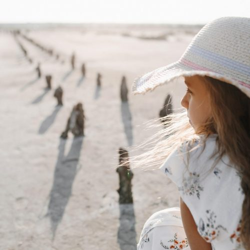 Back view of sad little girl on the sand beach on the sunny day dressed in hat, serious kid, child vacation, blonde caucasian girl